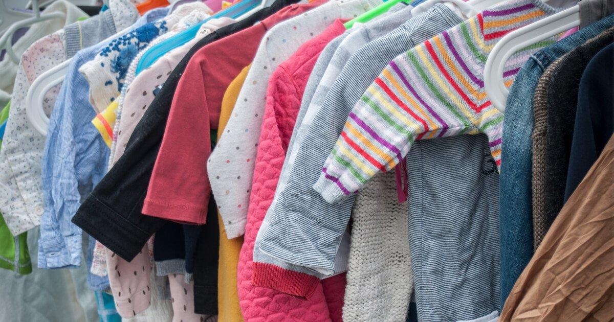 Babykleidung hängt an der Stange auf dem Kinderflohmarkt