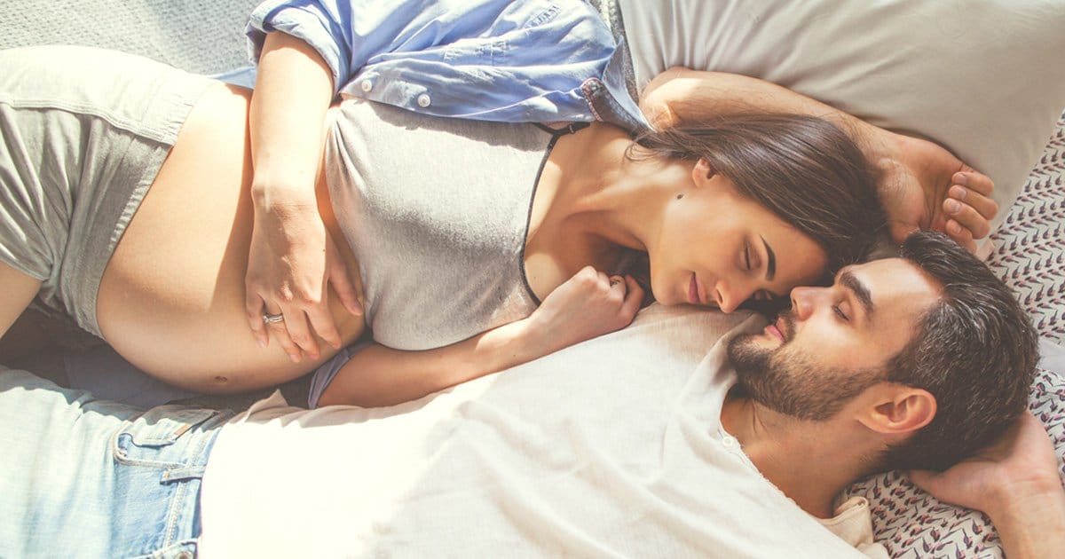 Mann kuschelt mit schwangerer Partnerin