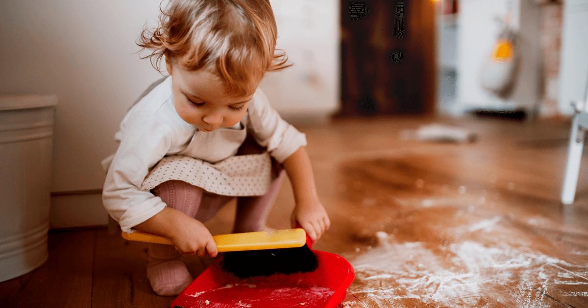 Mädchen putzt den Boden und übernimmt Haushaltsaufgaben