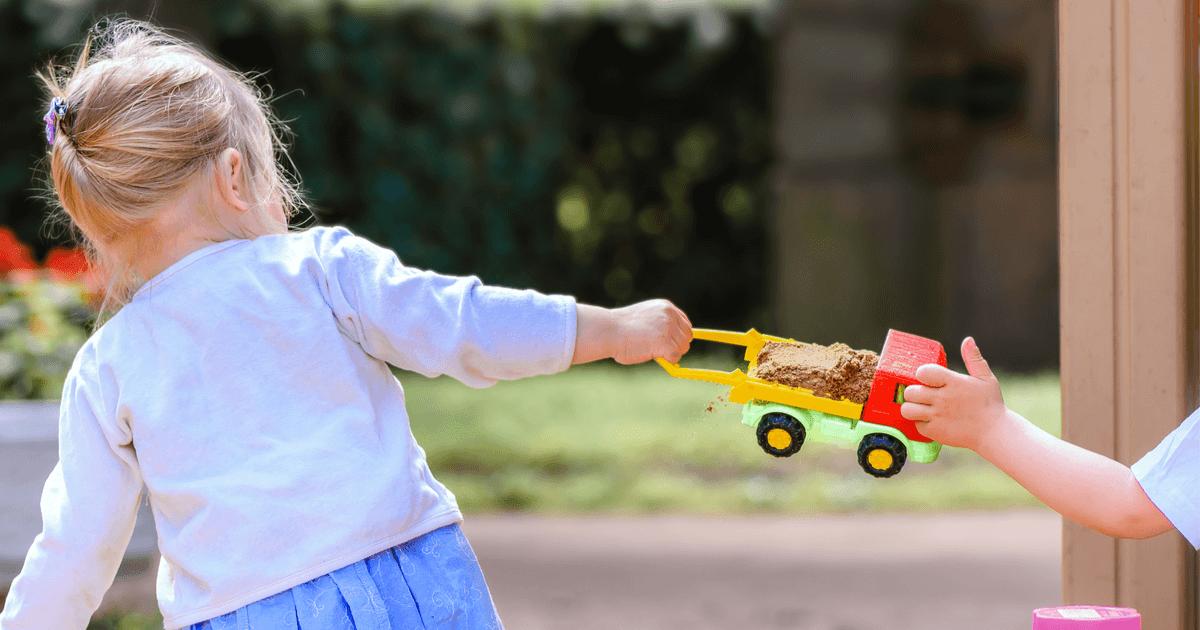 Streit um's Spielzeug: Zwei Kinder streiten sich um einen Spielzeug-Laster