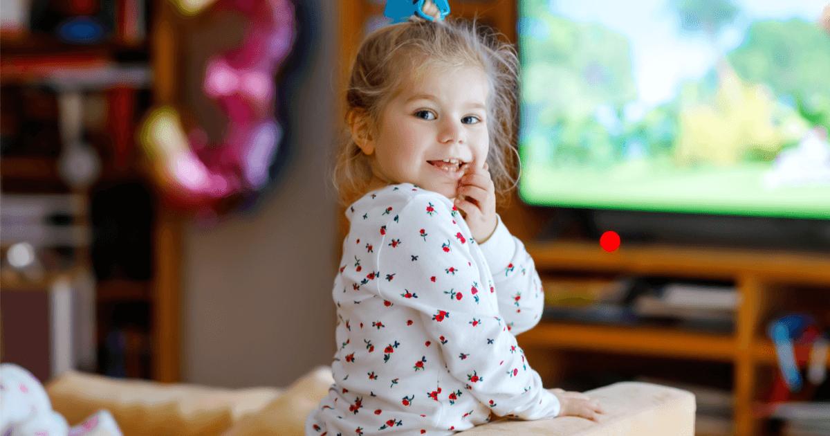 Fröhliches junges Mädchen vor einer Zeichentrickserie: Sind Videos und Fernsehen schädlich für Kinder?