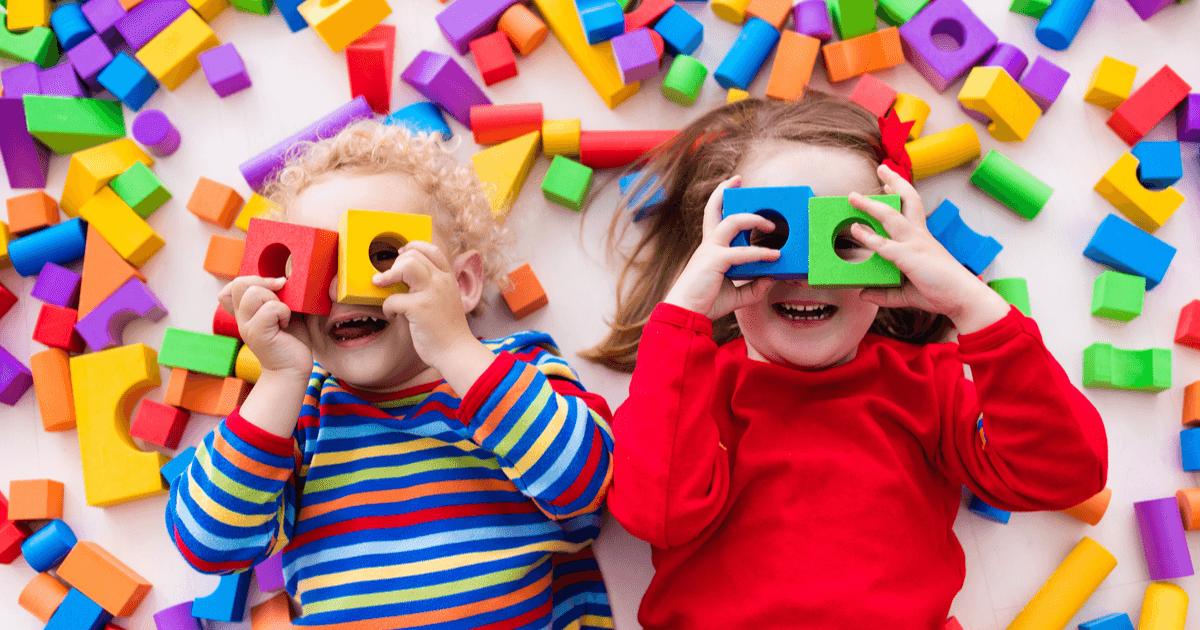 Selbstständig spielen lernen: Kinder liegen auf dem Boden und schauen durch Bausteine hindurch