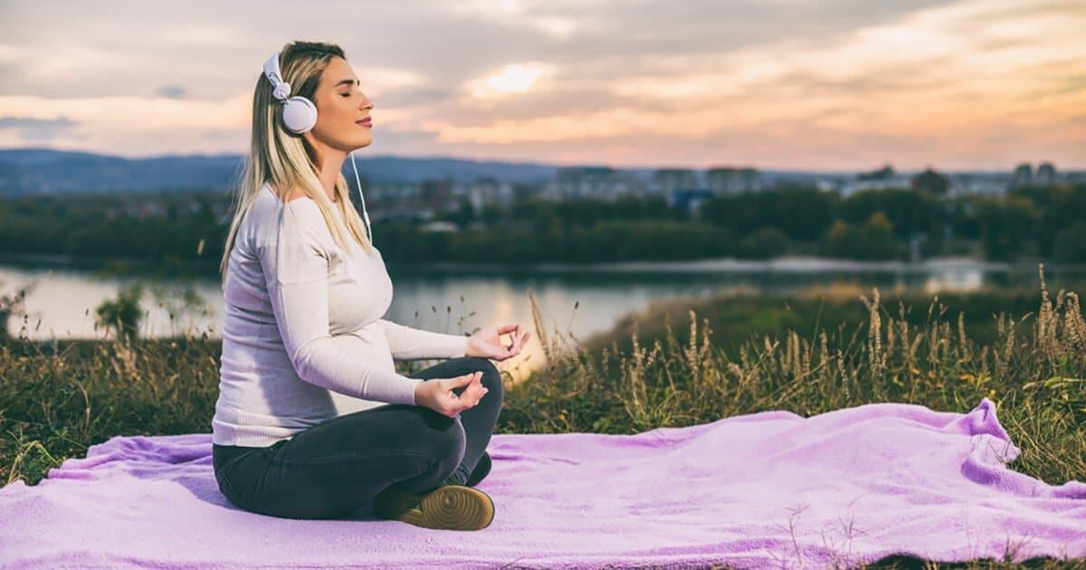 Schwangere meditiert am See