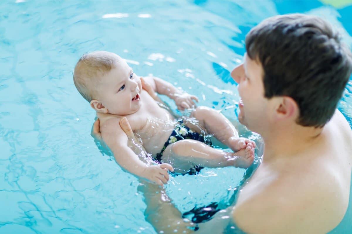 Papa hält sein Baby beim Schwimmen fest. Eine Schwimmhilfe für Babys ist nicht immer nötig, aber eine schöne Ergänzung