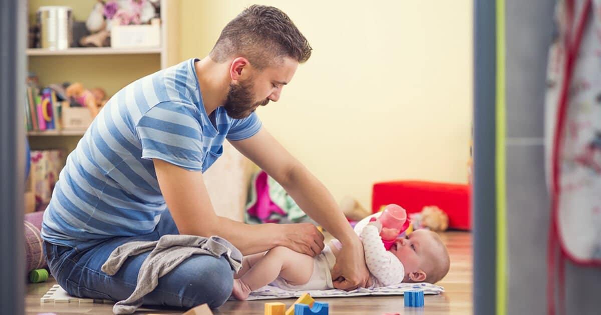 Vater wechselt Windeln seiner Tochter