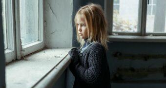 Vernachlässigender Erziehungsstil: Vernachlässigtes Mädchen schaut traurig aus dem Fenster